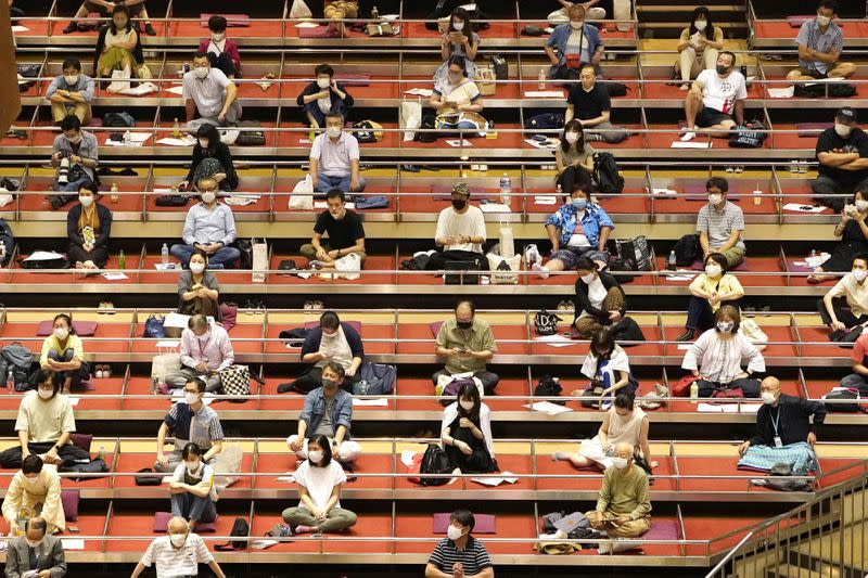 Spectators wearing protective masks practice social distancing as they watch the July Grand Sumo Tournament in Tokyo