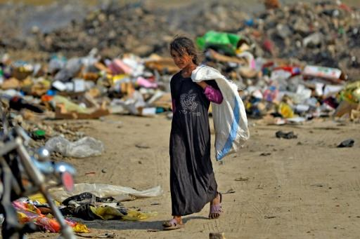 An Iraqi girl carrying a bag walks amidst piles of rubbish in a landfill in Diwaniyah, south of the capital Baghdad