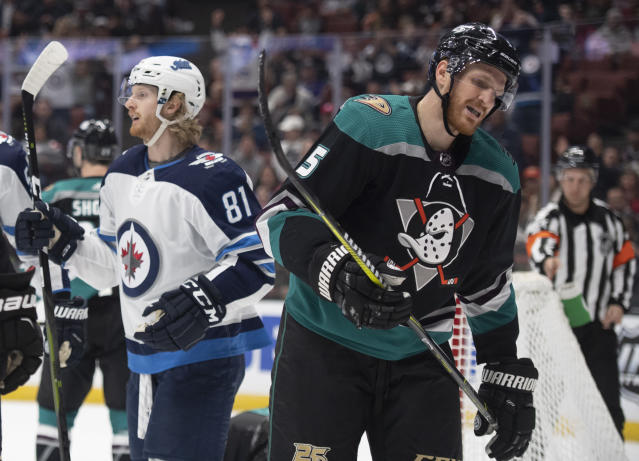 Anaheim Ducks defenseman Korbinian Holzer, right, reacts as Winnipeg Jets left wing Kyle Connor celebrates center Mark Scheifele's goal during the first period of an NHL hockey game in Anaheim, Calif., Wednesday, March 20, 2019. (AP Photo/Kyusung Gong)
