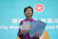 "Hong Kong Chief Executive Carrie Lam poses with copies of her policy address at a news conference in Hong Kong, Wednesday, Nov. 25, 2020. Lam lauded the city's new national security law on Wednesday as ""remarkably effective in restoring stability,"" despite criticism that it is severely narrowing the space for free speech and political opposition in the semi-autonomous Chinese territory. (AP Photo/Kin Cheung)"