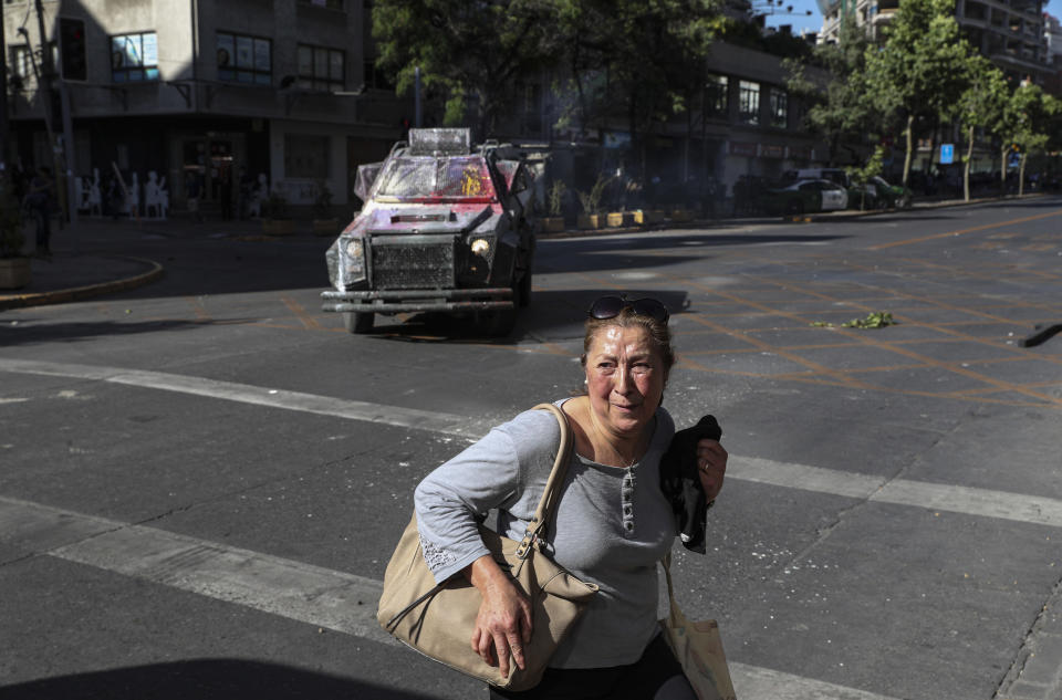 A woman crosses a street in front of an armored vehicle that is in pursuit of anti-government protesters, in Santiago, Chile, Thursday, Nov. 7, 2019. Chile's president announced on Thursday measures to increase security and toughen sanctions for vandalism following protests that have left at least 20 dead. (AP Photo/Esteban Felix)