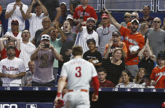 Fans react as Philadelphia Phillies' Bryce Harper (3) walks off the field after being tagged out at home plate during the sixth inning of a baseball game against the Miami Marlins, Sunday, April 14, 2019, in Miami. (AP Photo/Brynn Anderson)