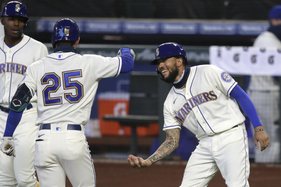 Seattle Mariners' Dylan Moore (25) is congratulated by J.P. Crawford after Moore's two-run home run against the Colorado Rockies during the first inning of a baseball game Sunday, Aug. 9, 2020, in Seattle. (AP Photo/Elaine Thompson)