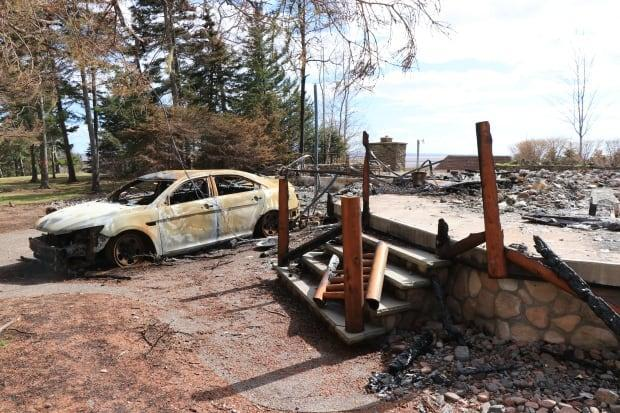The remains of a cottage and the burnt shell of a decommissioned RCMP cruiser are seen at a property in Portapique, N.S., that belonged to the gunman who killed 22 people on April 18 and 19.