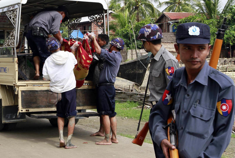 Myanmar policemen carry an unidentified body to a truck at a village in Sittwe, capital of Rakhine state in western Myanmar, where sectarian violence is impacting on the local population Monday June 11, 2012. The Buddhist-Muslim violence, which has left at least seven people dead and hundreds of homes torched since Friday, poses one the biggest tests yet for Myanmar's new government as it struggles to reform the nation after generations of military rule.(AP Photo/Khin Maung Win)