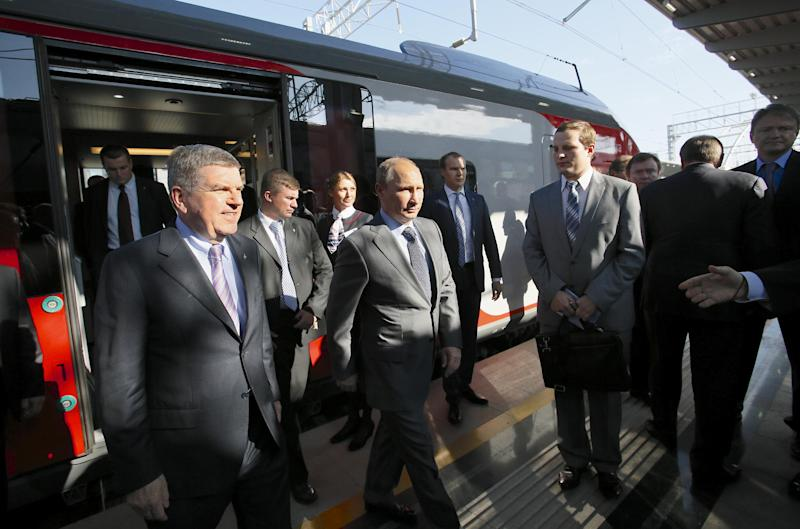 In this image taken Monday Oct. 28, 2013 Russian President Vladimir Putin, center, and International Olympic Committee President Thomas Bach, left, exit a commuter train at the newly built Adler railway station at the Black Sea resort of Sochi, southern Russia. Russian Railways is building the most expensive piece of Sochi infrastructure, a 48-kilometer (30-mile) highway and railroad link between the airport and the Alpine venues that has already cost the government 270 billion rubles ($8.5 billion). President Vladimir Putin was in Sochi to inaugurate the train station that serves as a hub for the link ahead of celebrations Wednesday marking exactly 100 days before the opening ceremony. (AP Photo/Alexander Zemlianichenko, Pool)