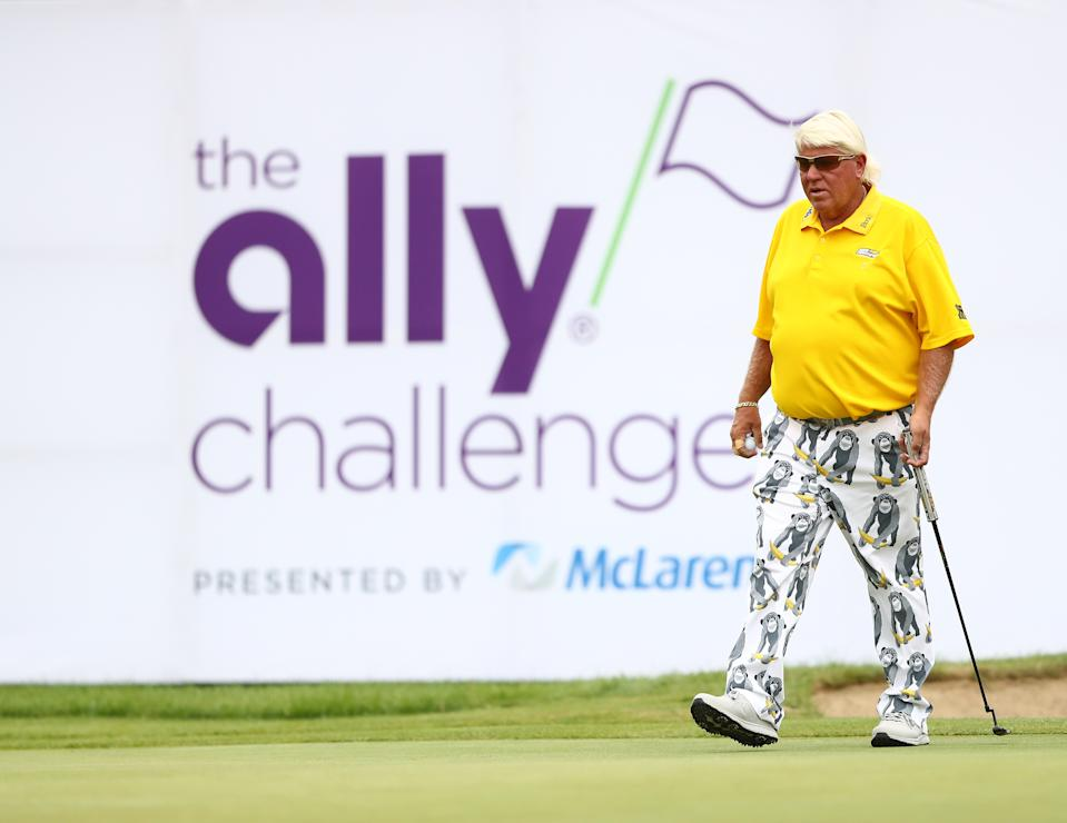 John Daly walks on the golf course in front of The Ally Challenge sign.