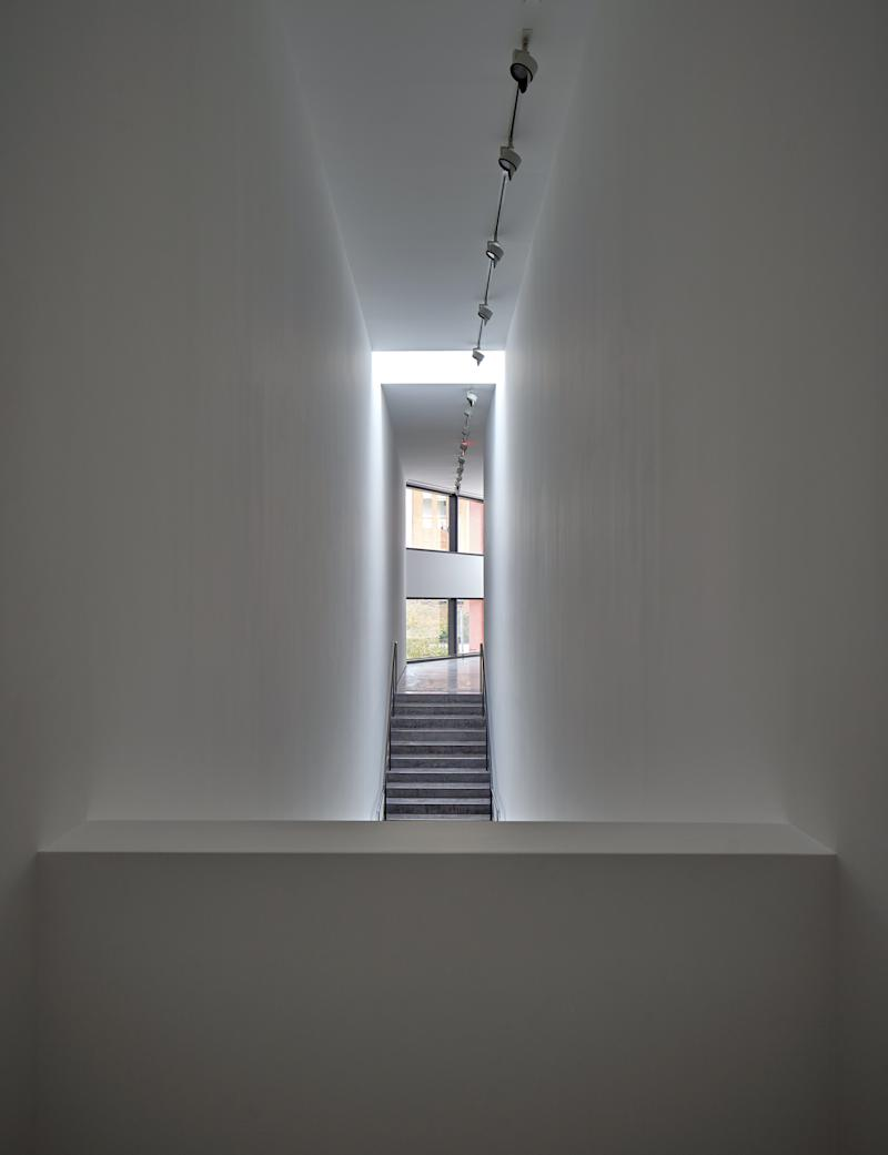 A skylight creates a halo above the main stairwell. The window at the end of the corridor is oriented to provide a vista of Chris Park, a green space dedicated to Linda Pace's late son.