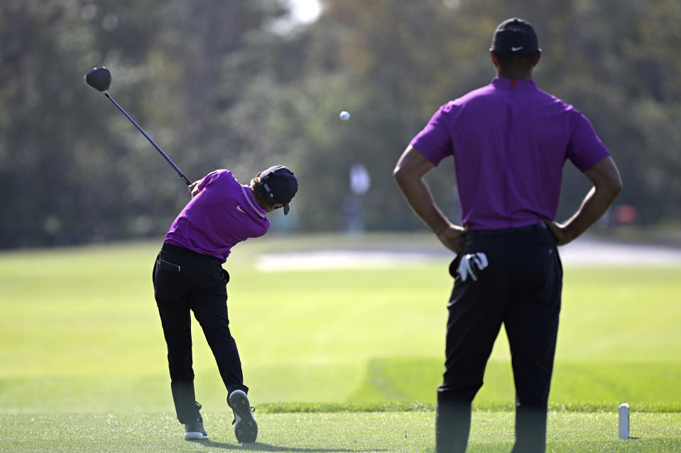 Tiger Woods, right, watches as his son Charlie tees off on the second hole during the first round of the PNC Championship golf tournament, Saturday, Dec. 19, 2020, in Orlando, Fla. (AP Photo/Phelan M. Ebenhack)