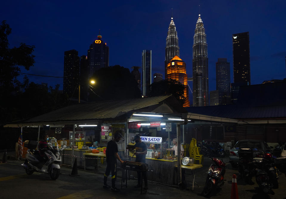A local food vendor prepares food with the Twin Towers in downtown Kuala Lumpur in the background background, Malaysia, Monday, Jan. 11, 2021. Prime Minister Muhyiddin Yassin says Malaysia's health care system is at a breaking point as he announced new movement curbs, including near-lockdown in Kuala Lumpur and several high-risk states to rein in a spike in coronavirus cases.(AP Photo/Vincent Thian)