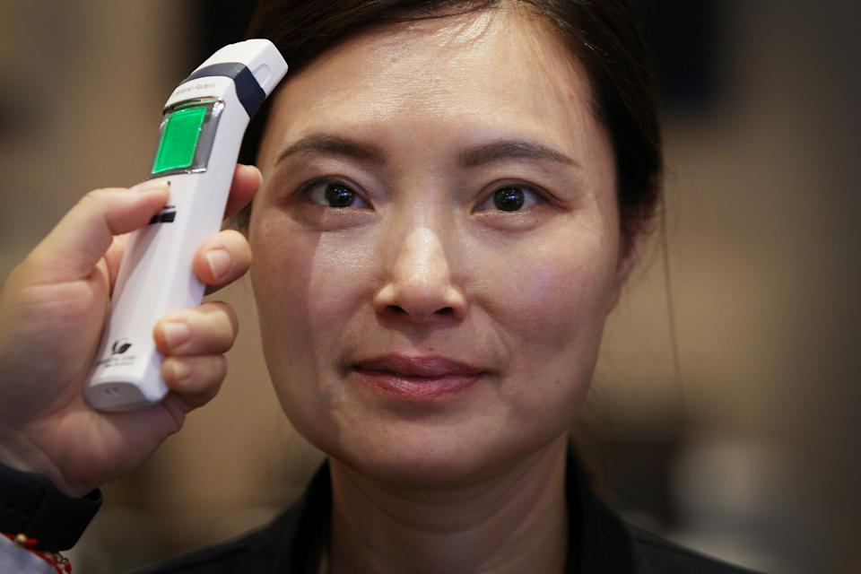 SYDNEY, AUSTRALIA - MARCH 05: Customer service worker Candy Huang has her temperature checked at the award winning Golden Century Seafood Restaurant in Chinatown on March 05, 2020 in Sydney, Australia. The Golden Century Seafood Restaurant has experienced a sudden drop in clientele of 50% this past week. To help safeguard against the coronavirus outbreak they have implemented daily temperature screening of all employees, hourly cleaning of all main public surfaces, including all handrails and the provision of customer hand sanitiser. Chinese restaurant owners across Sydney say the current restrictions in place on people travelling from mainland China to Australia means they have lost the majority of their usual clientele - Chinese tourists and students. A number of restaurants have already gone into liquidation. (Photo by Lisa Maree Williams/Getty Images)