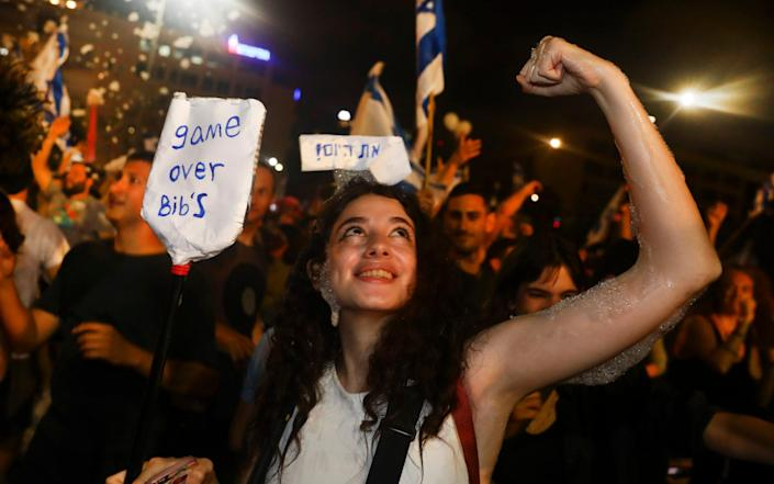"""Israelis celebrate the swearing in of a new government on June 13. The sign reads: """"Game over Bibi"""" - a reference to a popular nickname for Mr Netanyahu - Oded Balilty/AP"""