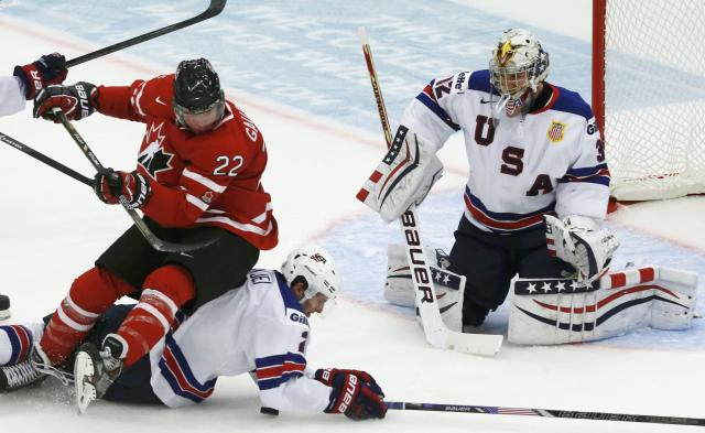 Canada's Frederik Gauthier (22) falls on United States Brady Skjei in front of U.S. goalie Jon Gillies during the first period of their IIHF World Junior Championship ice hockey game in Malmo, Sweden, December 31, 2013. REUTERS/Alexander Demianchuk (SWEDEN - Tags: SPORT ICE HOCKEY)