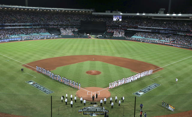 The teams line up for the national anthems before the Major League Baseball opening game between the Los Angeles Dodgers and Arizona Diamondbacks at the Sydney Cricket Ground in Sydney, Australia Saturday, March 22, 2014. (AP Photo/Rick Rycroft)