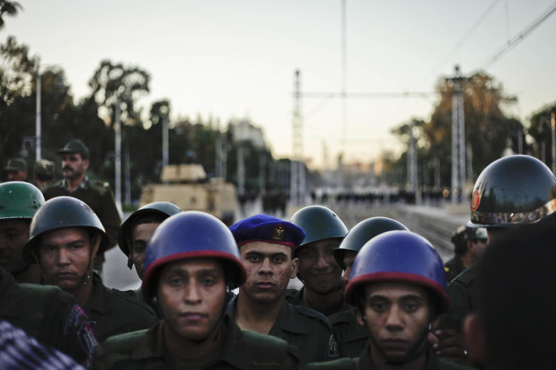 Egyptian army soldiers stand guard during a demonstration in front of the presidential palace in Cairo, Egypt, Friday, Dec. 7, 2012. Egypt's political crisis spiraled deeper into bitterness and recrimination on Friday as large crowds of the Egyptian President Mohammed Morsi's opponents marched to his palace to increase pressure after he rejected their demands. (AP Photo/Nariman El-Mofty)