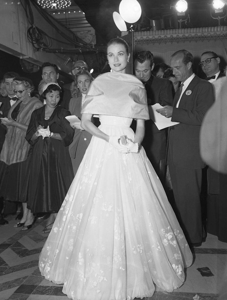 <p>Speaking of royalty, Grace literally looked like a princess in a ballgown, capelet, and white-gloves at the '56 ceremony. She wore her hair in a sleek bun, and later took the outerwear off on stage to reveal a gorgeous criss-cross neckline.</p>