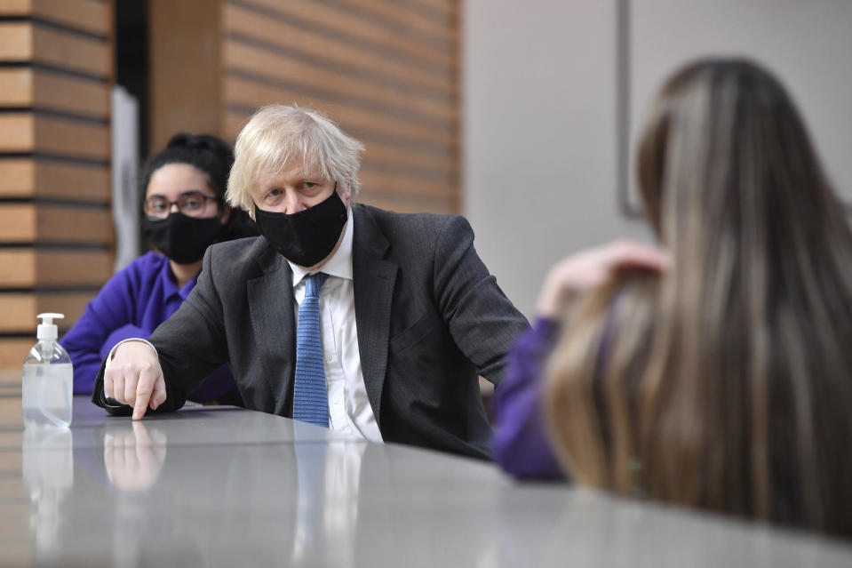 Britain's Prime Minister Boris Johnson meets with Year 11 students in the canteen during a visit to Accrington Academy in Accrington, England, Thursday, Feb. 25, 2021, as they prepare for the return of all pupils on March 8. (Anthony Devlin/Pool Photo via AP)
