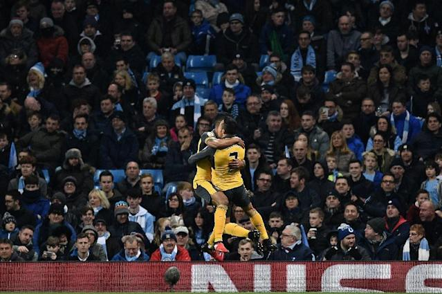 Arsenal's midfielder Theo Walcott (L) celebrates scoring with striker Alexis Sanchez during an English Premier League football match against Manchester City on December 18, 2016 (AFP Photo/Oli SCARFF )