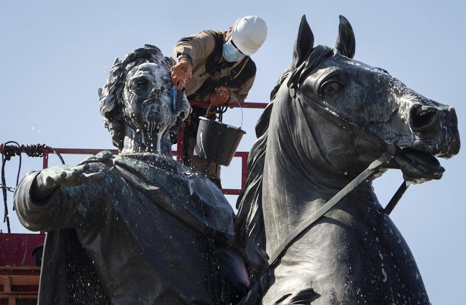 A worker wearing a face mask washes the equestrian statue of the Russian Tsar Peter the Great known as the Bronze Horseman in St.Petersburg, Russia. Source: AP
