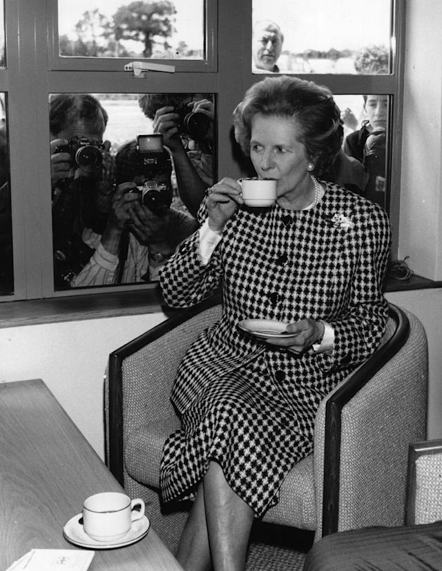 6th June 1987: British Conservative Prime Minister, Margaret Thatcher, enjoys a cup of tea at the opening of the South Mimms Motorway service area, watched by the press. (Photo by Keystone/Getty Images)