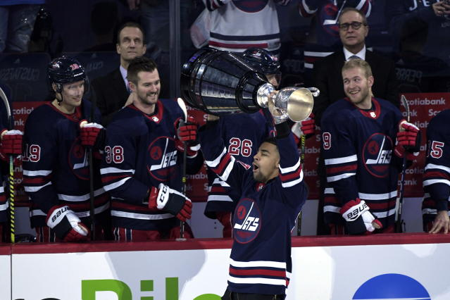 Andrew Harris of the CFL champion Winnipeg Blue Bombers carries out the Grey Cup prior to the puck drop at the NHL game between the Winnipeg Jets and Dallas Stars before the first period of an NHL hockey game, Tuesday, Dec. 3, 2019 in Winnipeg, Manitoba. (Fred Greenslade/The Canadian Press via AP)