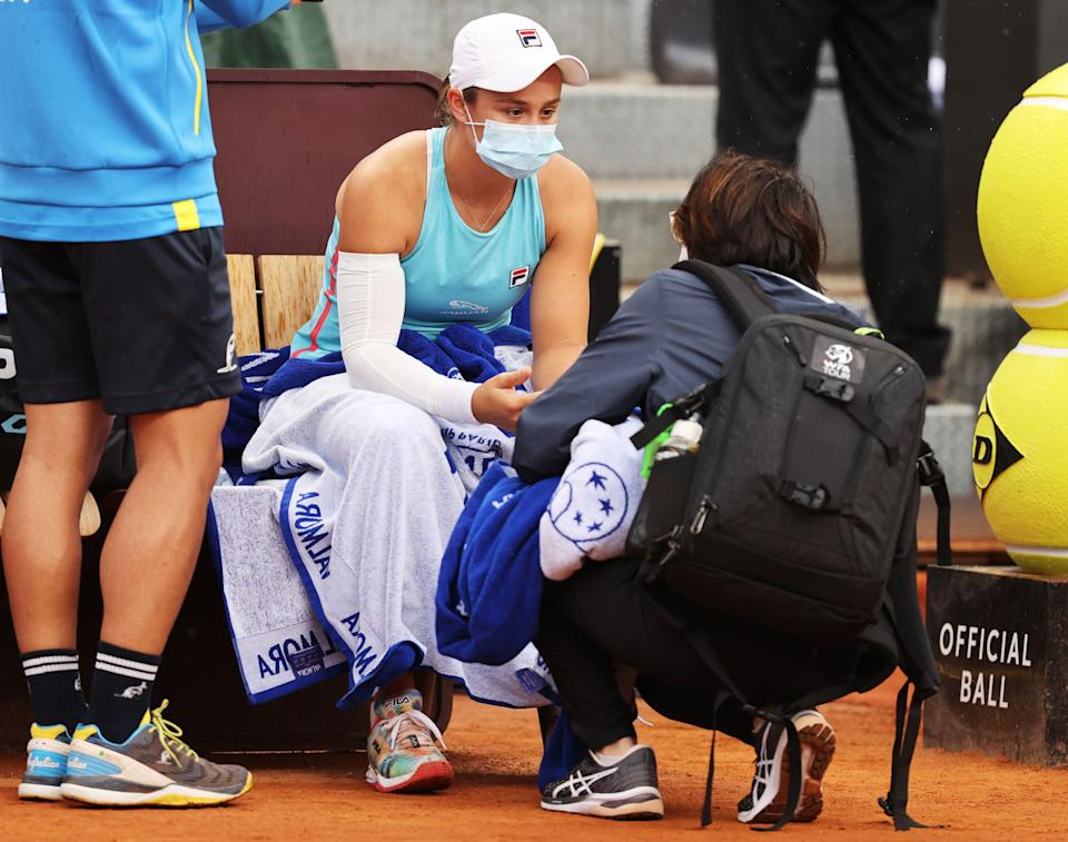 Ash Barty wearing a mask and speaking to the trainer at the Italian Open.