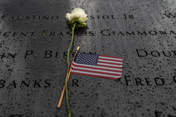 Flowers and American flags rest among the names of the fallen on the south pool at the National September 11 Memorial & Museum, Thursday, Sept. 9, 2021, in the Manhattan borough of New York. (AP Photo/John Minchillo)