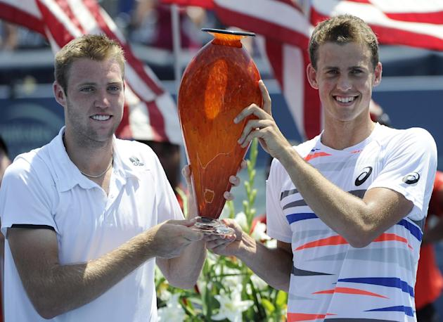 Jack Sock, left, holds the trophy with playing partner Vasek Pospisil after they defeated Steve Johnson and Sam Querrey to win the doubles final in Atlanta in July. (AP Photo/David Tulis)