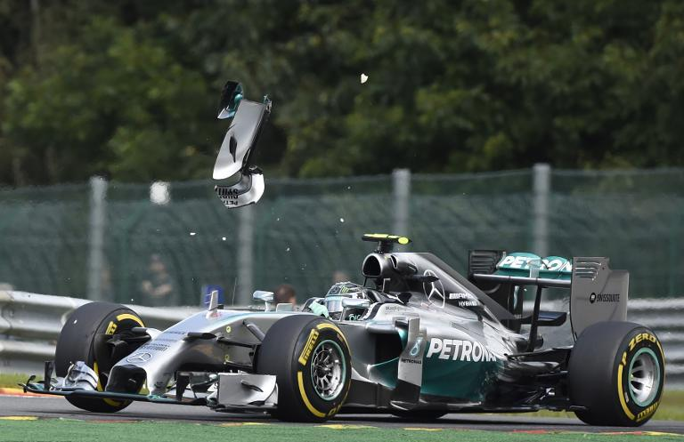 A piece of wing flys over Mercedes-AMG's German driver Nico Rosberg after a collision with teammate Mercedes-AMG's British driver Lewis Hamilton at the Spa-Francorchamps ciruit in Spa on August 24, 2014