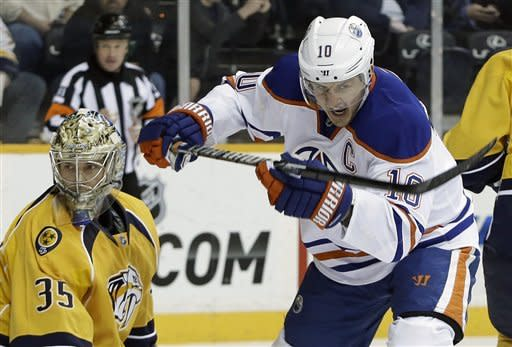 Edmonton Oilers center Shawn Horcoff (10) celebrates after a shot by teammate Corey Potter, unseen, got past Nashville Predators goalie Pekka Rinne (35), of Finland, for a goal in the first period of an NHL hockey game on Monday, March 25, 2013, in Nashville, Tenn. (AP Photo/Mark Humphrey)
