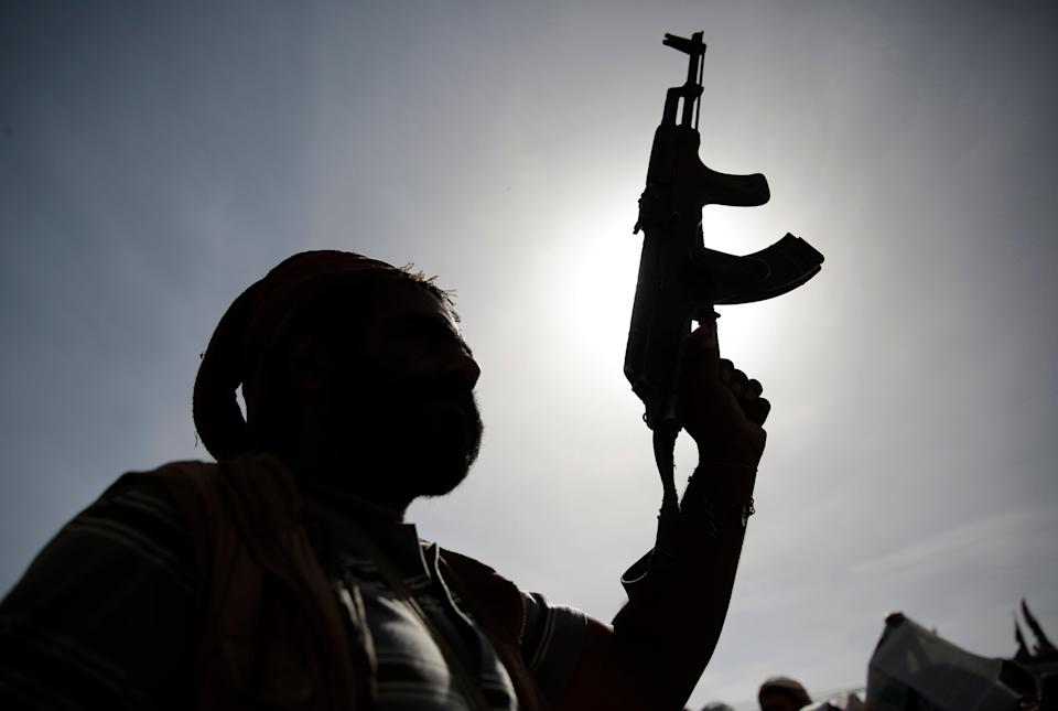 A silhouette of a Houthi supporter holds his weapon during a rally last month (AP)