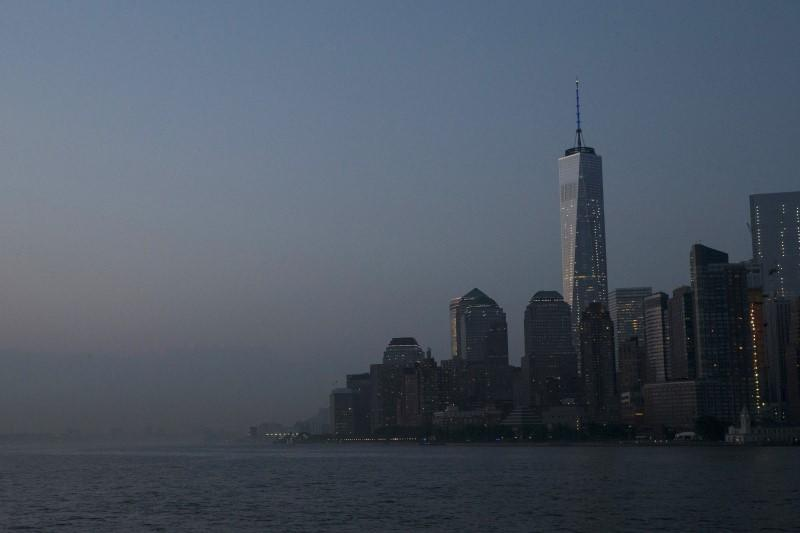 A view from New York Harbor shows the Lower Manhattan, New York City skyline and the One World Trade Center tower just after sunset