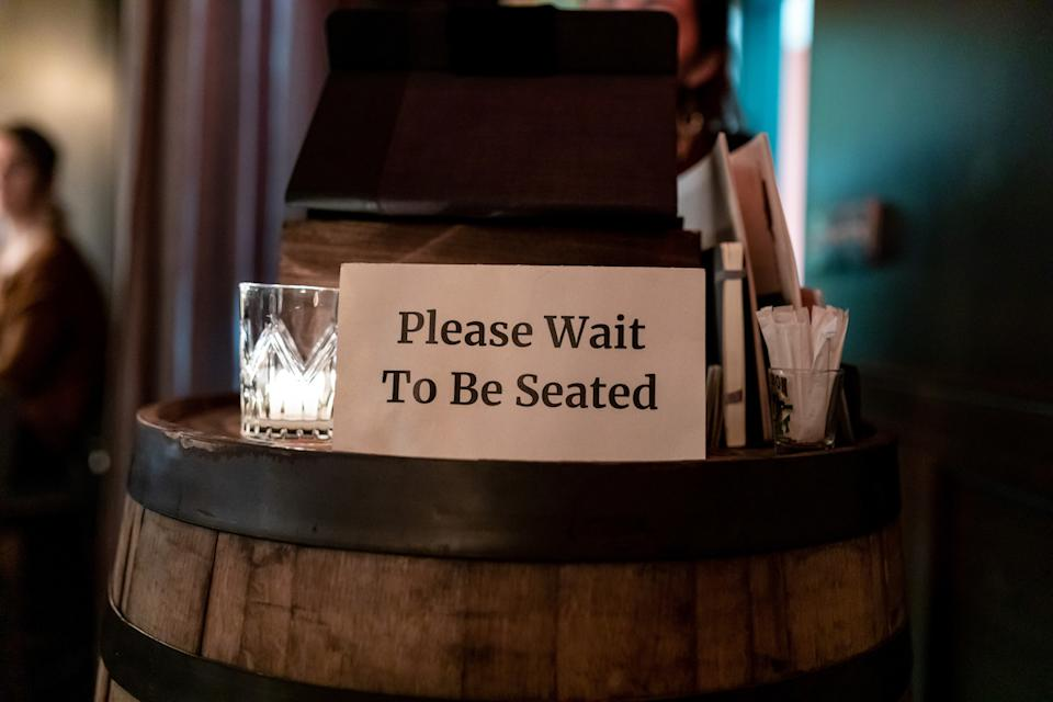 """Posted sign on a hostess stand read """" Please Wait to be seated"""""""