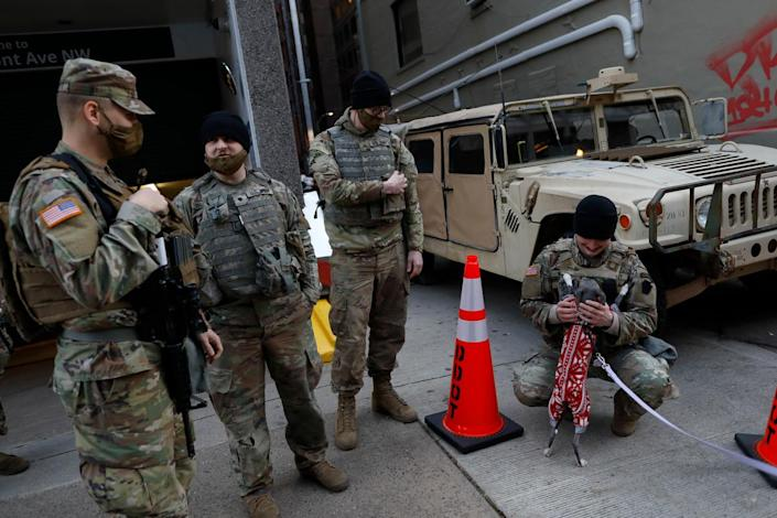 A National Guardsman gets a greeting from a passing dog, as a few Guard posts remain along downtown streets one day after the inauguration of President Joe Biden, Thursday, Jan. 21, 2021, in Washington. (AP Photo/Rebecca Blackwell)