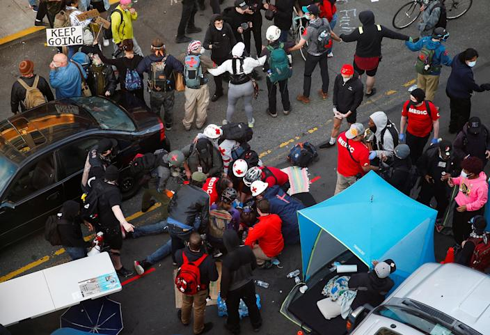 Image: Medics tend to a man who was shot in the arm by a driver of a black vehicle at a protest against racial inequality in the aftermath of the death in Minneapolis police custody of George Floyd, in Seattle, Washington (Lindsey Wasson / Reuters)