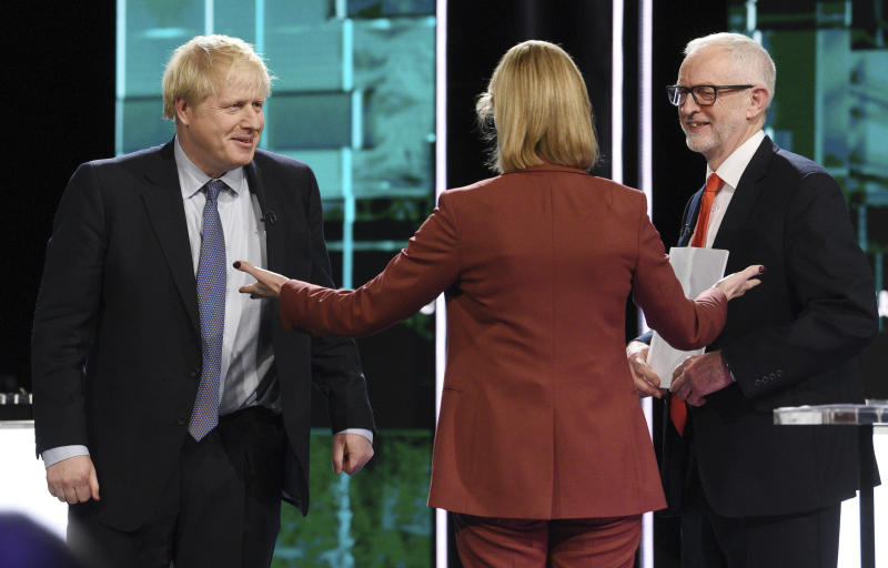 In this photo issued by ITV, showing Boris Johnson, left, and Jeremy Corbyn, right, with TV debate adjudicator Julie Etchingham, following their election head-to-head debate live on TV, in Salford, Manchester, England, Tuesday, Nov. 19, 2019.  Prime Minister Boris Johnson and Jeremy Corbyn are set to go head-to-head in their first live televised debate Tuesday evening, as the UK prepares for a General Election on Dec. 12. (ITV via AP)