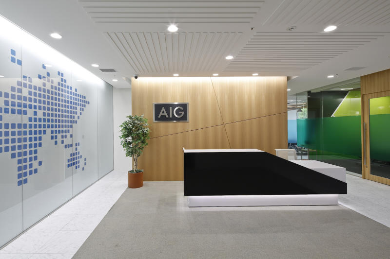 Office lobby with AIG logo on wood-paneled wall.