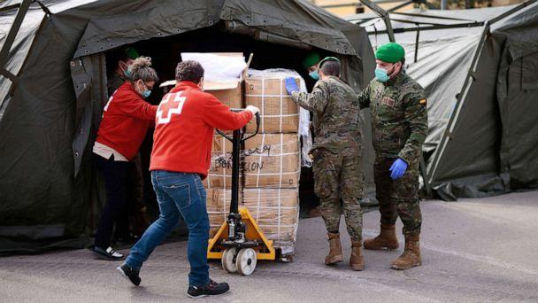 PHOTO: Spanish soldiers and Red Cross members gather equipment for a temporary hospital being set up at the Fira Barcelona Montjuic centre in Barcelona, Spain, March 25, 2020, during the new coronavirus epidemic. (Pau Barrena/AFP via Getty Images)