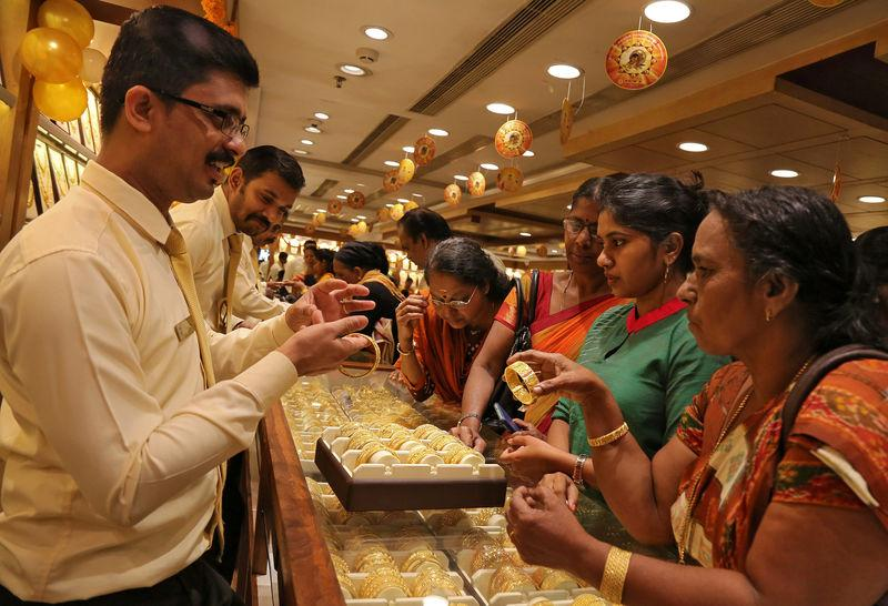 A salesman shows gold bangles to customer inside a jewellery showroom on the occasion of Akshaya Tritiya, a major gold buying festival, in Kochi
