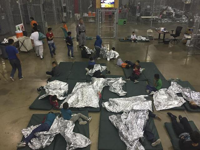 Detained immigrants are separated by chain-linked fencing according to age and gender -- with young siblings split up -- for up to 72 hours (AFP Photo/Handout)