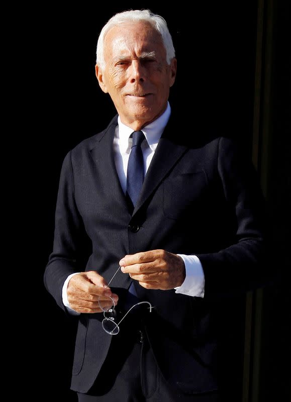 FILE PHOTO: FILE PHOTO: Italian designer Armani poses for photographers as he leaves the opening ceremony of the Armani Hotel Milano in Milan