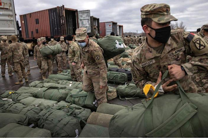 US Army soldiers retrieve their duffel bags after they returned home from a 9-month deployment to Afghanistan on December 10, 2020 at Fort Drum, New York.