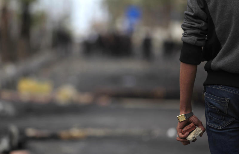 An Egyptian protester holds stones during clashes with riot police near a state security building in Port Said, Egypt, Thursday, March 7, 2013. Clashes between protesters and police continued into a fifth day on Thursday in the restive Egyptian city of Port Said. (AP Photo/Khalil Hamra)