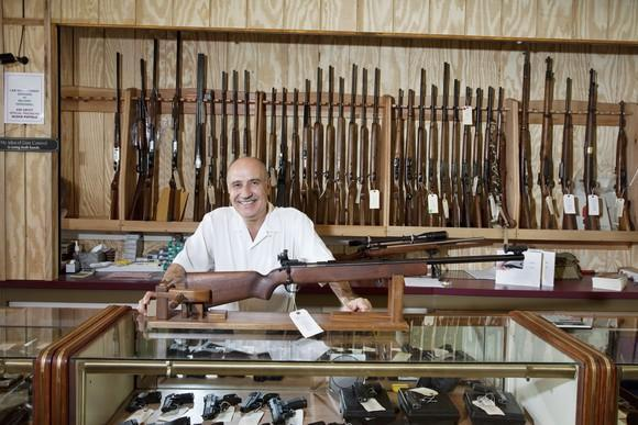 Firearms dealer in front of a display