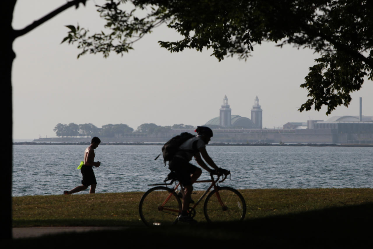 "An early morning cyclist and a jogger head to downtown along the shore of Lake Michigan Wednesday, July 20, 2011 in Chicago. Much of the United States is trapped under a heat ""dome"" caused by a huge area of high pressure that's compressing hot, moist air beneath it, leading to miserable temperatures in the mid-90s to low 100s and heat-index levels well above 100 degrees. (AP Photo/Kiichiro Sato)"