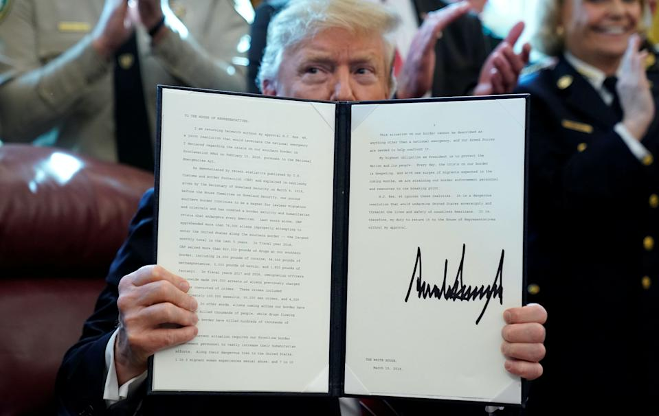 U.S. President Donald Trump holds up his veto of the congressional resolution to end his emergency declaration to get funds to build a border wall after signing it in the Oval Office of the White House in Washington, U.S., March 15, 2019. (Photo: REUTERS/Jonathan Ernst)