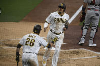 San Diego Padres' Manny Machado (13) is congratulated by Austin Nola (26) as he scores during the third inning of a baseball game against the St. Louis Cardinals, Friday, May 14, 2021, in San Diego. (AP Photo/Denis Poroy)