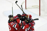 New Jersey Devils center Michael McLeod (20) surrounds teammates, including New Jersey Devils center Pavel Zacha (37), center, (seen only by his helmet) after Zacha scored a game-winning goal in playoff-bound Boston Bruins, Tuesday, May 4, 2021, in Newark, N.J. (AP Photo/Kathy Willens)