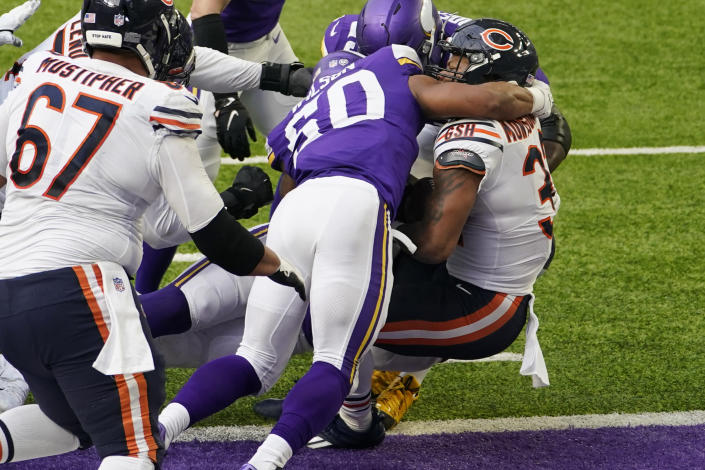 Chicago Bears running back David Montgomery, right, scores on a 1-yard touchdown run ahead of Minnesota Vikings linebacker Eric Wilson (50) during the first half of an NFL football game, Sunday, Dec. 20, 2020, in Minneapolis. (AP Photo/Jim Mone)