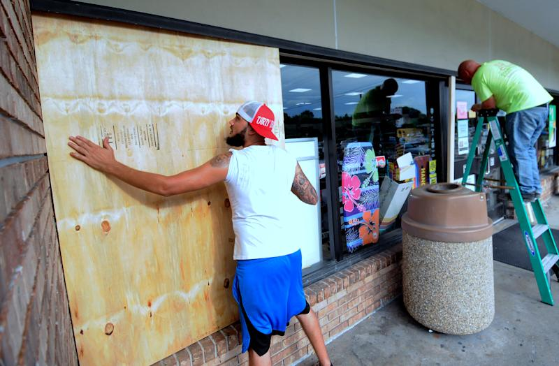 Workers install protective sheets of plywood over the windows of a convenience store in preparation for the arrival of Hurricane Dorian. (Photo: Paul Hennessy/SOPA Images/LightRocket via Getty Images)